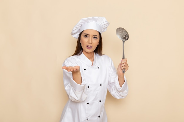 Front view of young female cook in white cook suit holding silver big spoon on light white wall