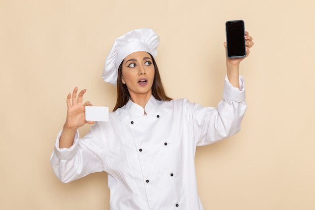 Front view of young female cook in white cook suit holding smartphone and card on light-white wall