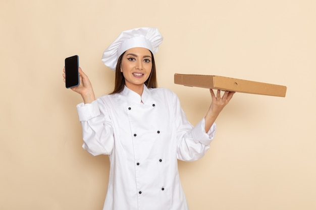 Front view of young female cook in white cook suit holding smartphone and food box on white wall