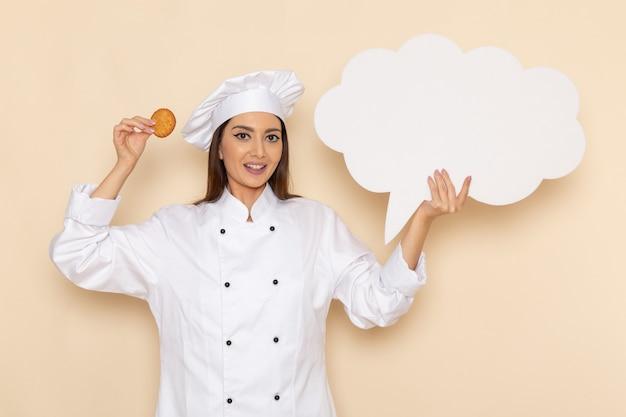 Vista frontale del giovane cuoco femminile in vestito bianco del cuoco che tiene segno e biscotto bianchi sulla parete bianca