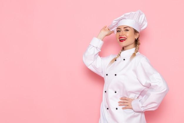 Giovane cuoco femminile di vista frontale in vestito bianco del cuoco che posa appena con il sorriso sulla foto del lavoro di lavoro di cucina del cuoco dello spazio rosa