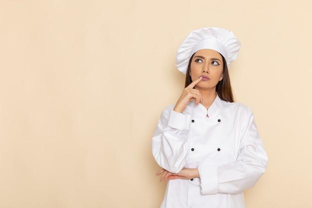 Vista frontale della giovane cuoca in tuta bianca da cuoco solo pensando alla parete bianco-chiaro