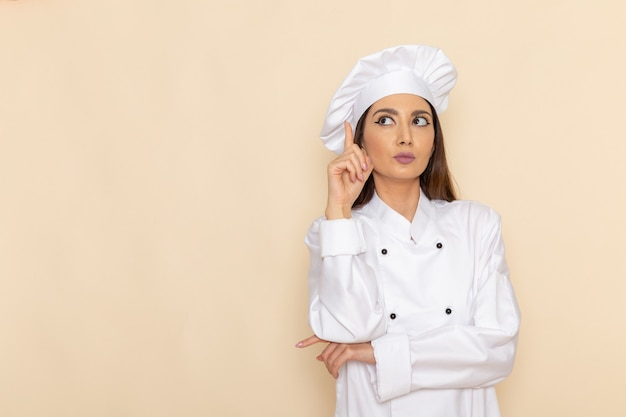 Front view of young female cook in white cook suit posing and thinking on light-white wall