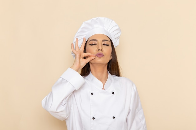 Front view of young female cook in white cook suit showing delicious sign on light-white wall