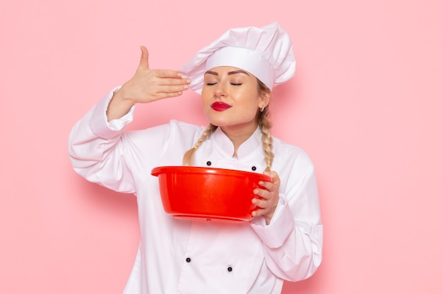 Front view young female cook in white cook suit smelling red plastic bowl on the pink space cook