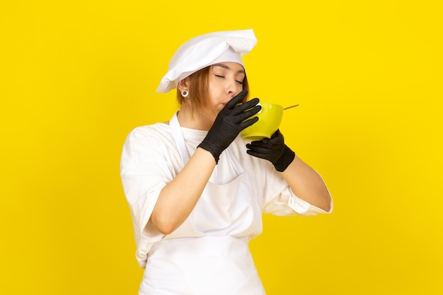 A front view young female cook in white cook suit and white cap in black gloves holding green plate eating spaghetti on the yellow