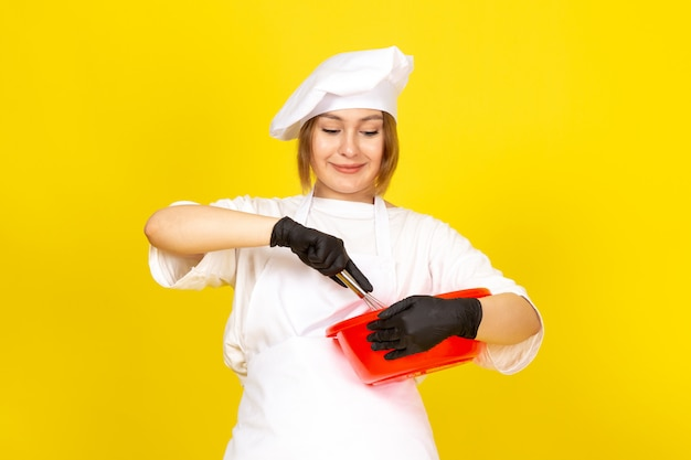A front view young female cook in white cook suit and white cap in black gloves holding red bowl mixing it up on the yellow
