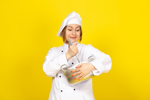 A front view young female cook in white cook suit and white cap holding round silver pan smiling on the yellow