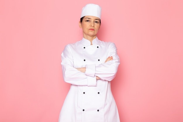 A front view young female cook in white cook suit white cap posing displeased serious look