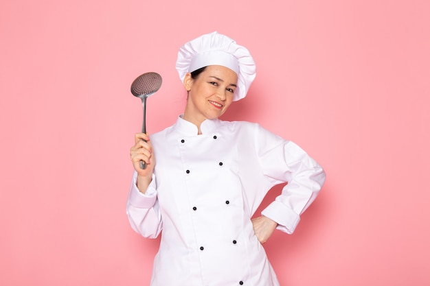 A front view young female cook in white cook suit white cap posing holding big silver spoon smiling