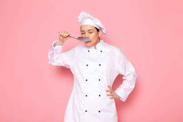 A front view young female cook in white cook suit white cap posing holding big silver spoon tastying meal