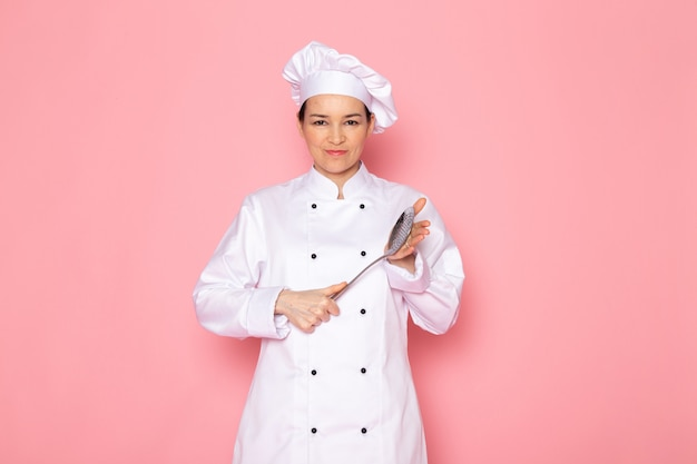 A front view young female cook in white cook suit white cap posing holding big silver spoon