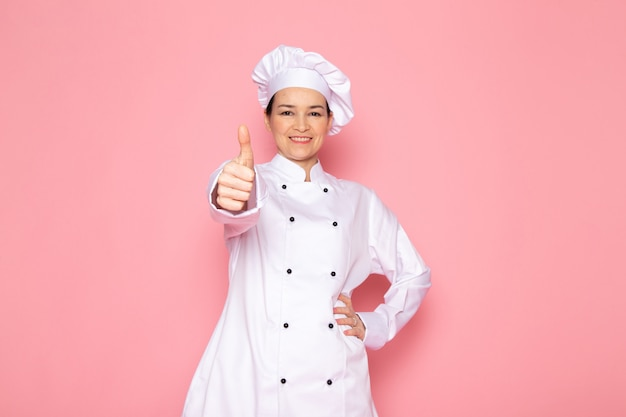 A front view young female cook in white cook suit white cap smiling posing happy