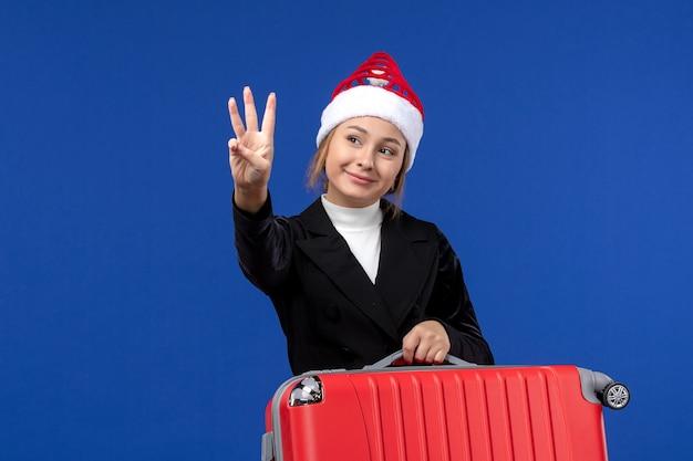 Вид спереди молодая женщина, подсчитывающая номер на синей стене, праздник, отпуск, женщина
