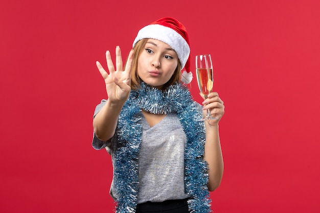 赤い壁の色のクリスマス休暇の数を示す正面図若い女性