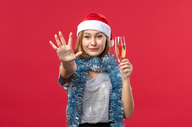 Front view young female counting showing number on red wall color christmas holiday