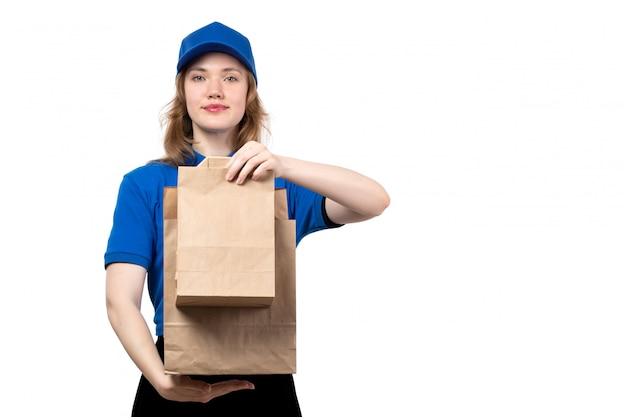 A front view young female courier in blue shirt blue cap and black trousers holding delivery food packages on white
