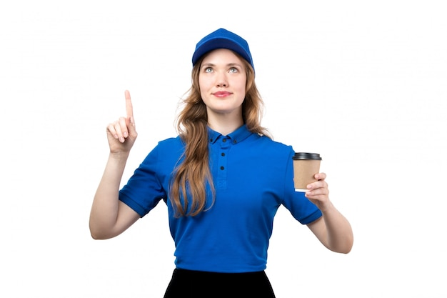 A front view young female courier in blue shirt blue cap and black trousers smiling looking into the skies holding cup of coffee on white