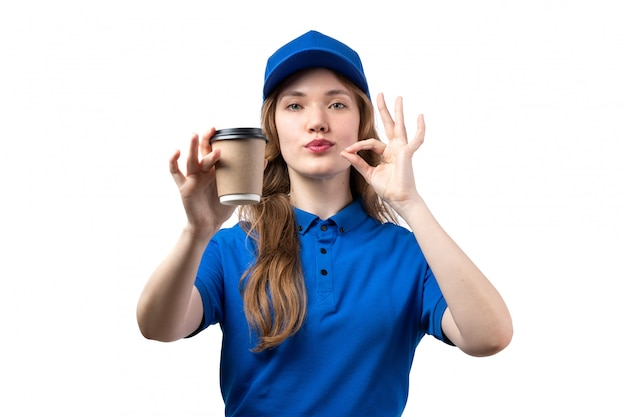 A front view young female courier in blue shirt blue cap holding coffee cup showing tasty sign on white