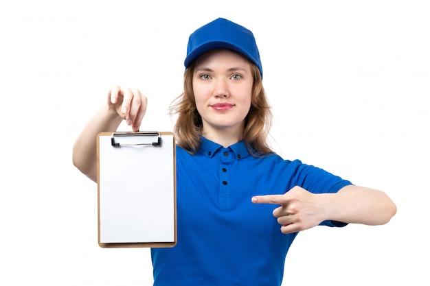 Un giovane corriere femminile di vista frontale in berretto blu della camicia blu che sorride blocco note sorridente della tenuta su bianco
