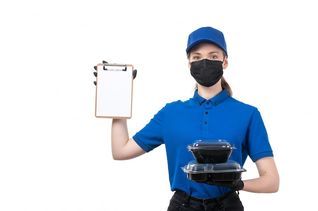 A front view young female courier in blue uniform black gloves and black mask holding food delivery bowls and notepad