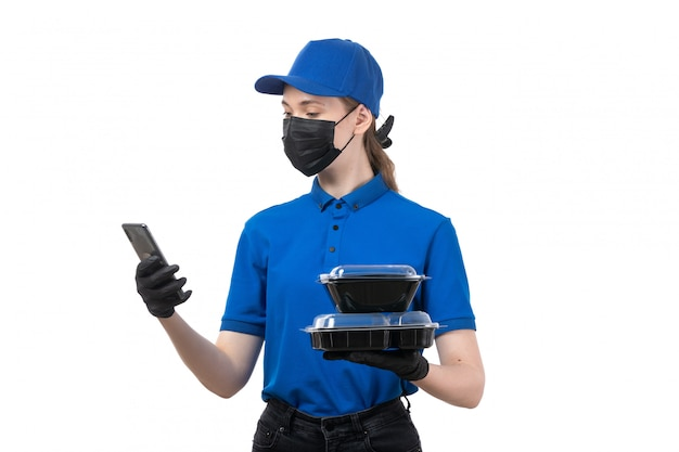 A front view young female courier in blue uniform black gloves and black mask holding food delivery bowls and phone