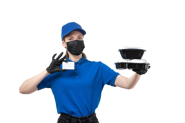A front view young female courier in blue uniform black gloves and black mask holding food delivery bowls and white card