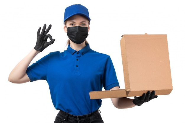 A front view young female courier in blue uniform black gloves and black mask holding food delivery package