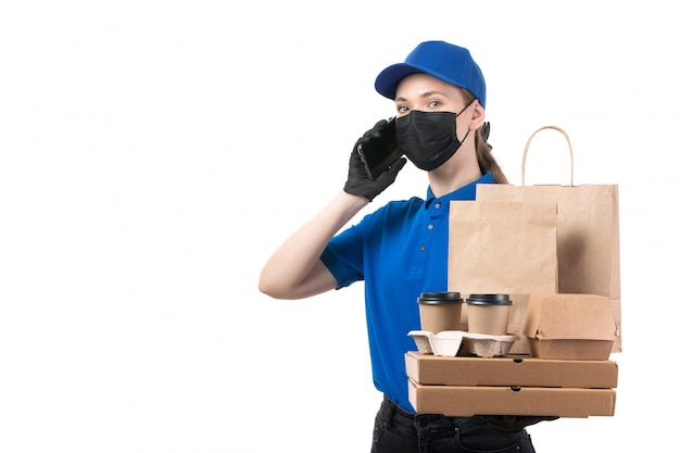 A front view young female courier in blue uniform black gloves and black mask holding food delivery packages and smartphone