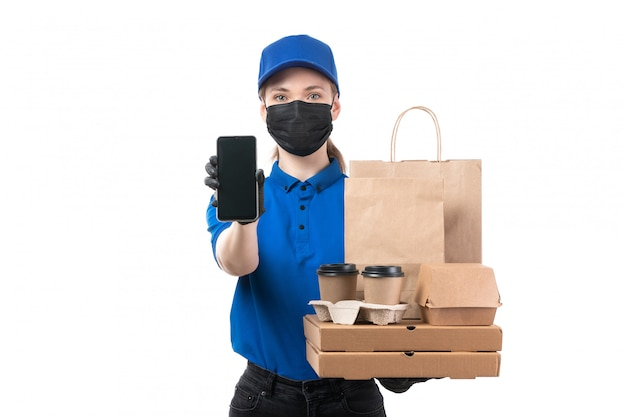 A front view young female courier in blue uniform black gloves and black mask holding food delivery packages