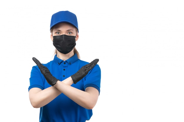 A front view young female courier in blue uniform black gloves and black mask showing ban sign
