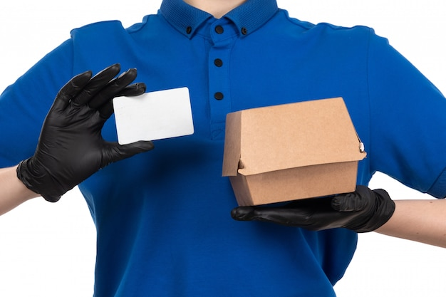 A front view young female courier in blue uniform black mask and gloves holding food delivery package