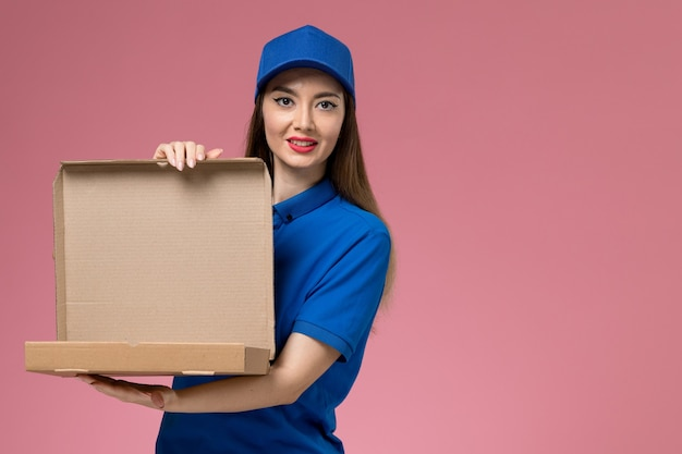 Front view young female courier in blue uniform and cape holding food box and opening it on pink wall