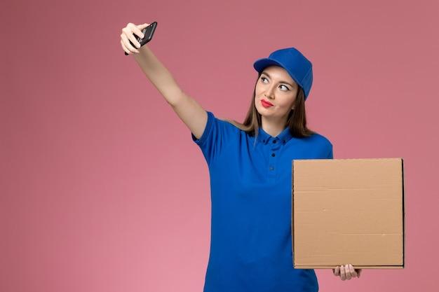 Giovane corriere femminile di vista frontale in uniforme blu e contenitore dell'alimento della tenuta del capo che prende foto con esso sulla parete rosa
