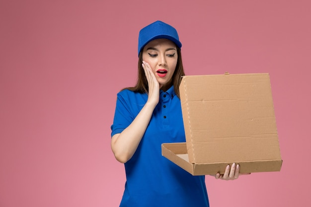 Front view young female courier in blue uniform and cape holding food delivery box and opening it on the pink wall