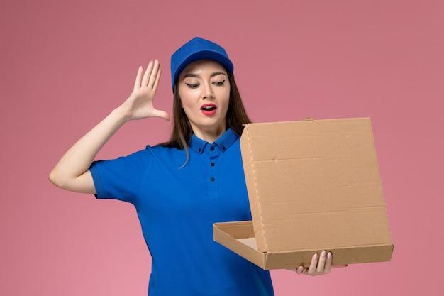 Vista frontale giovane corriere femminile in uniforme blu e mantello che tiene la scatola di consegna del cibo aprendolo sulla parete rosa