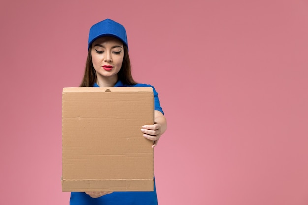 Front view young female courier in blue uniform and cape holding food delivery box opening on light pink wall