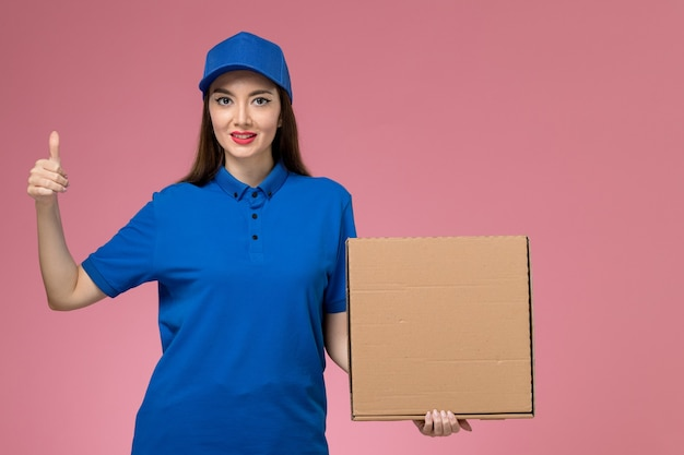 Front view young female courier in blue uniform and cape holding food delivery box on the pink wall