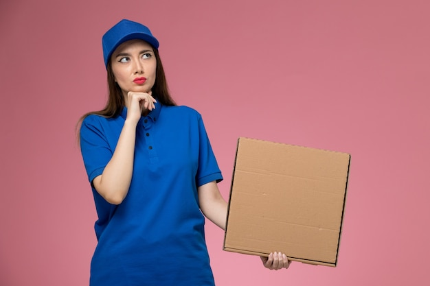 Front view young female courier in blue uniform and cape holding food delivery box thinking on pink wall