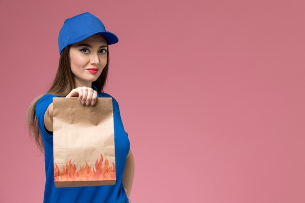 Front view young female courier in blue uniform and cape holding paper food package on the light-pink wall  worker