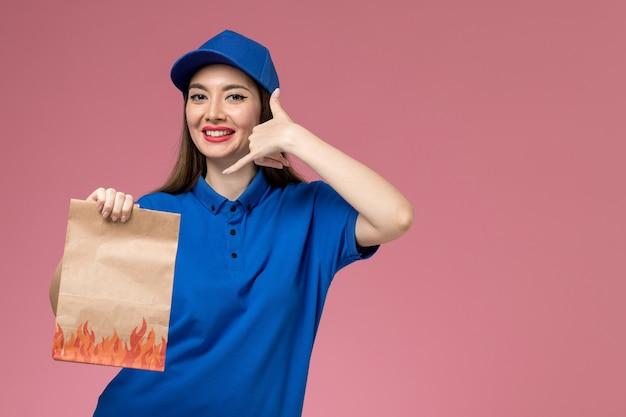 Giovane corriere femminile di vista frontale in uniforme blu e mantello che tiene il pacchetto alimentare di carta con il sorriso sul pavimento rosa