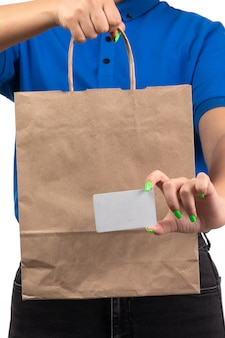A front view young female courier in blue uniform holding food delivery package and white card