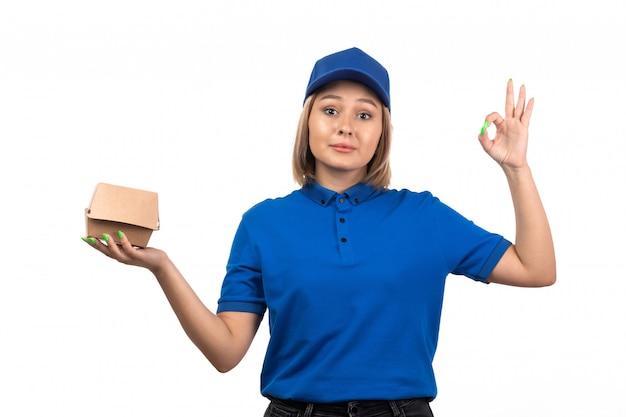 Un giovane corriere femminile di vista frontale in uniforme blu che tiene il pacchetto di consegna dell'alimento