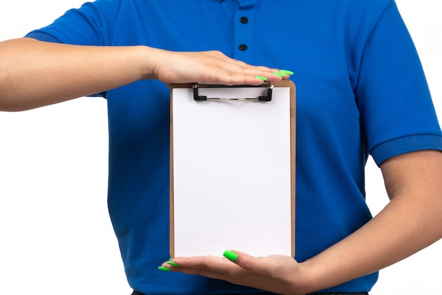A front view young female courier in blue uniform holding notepad for signatures