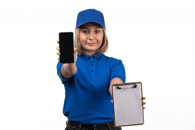 A front view young female courier in blue uniform holding phone and notepad