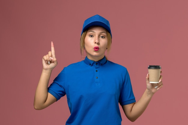 Giovane corriere femminile di vista frontale in uniforme blu che posa che tiene la tazza di caffè marrone di consegna, foto dell'operaio di lavoro della donna di consegna dell'uniforme di servizio
