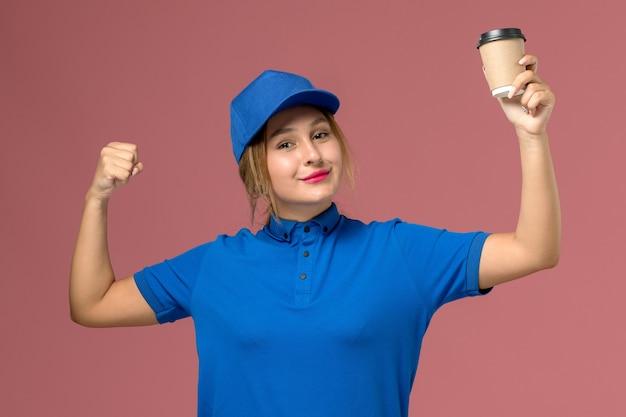 Giovane corriere femminile di vista frontale in uniforme blu che posa tenendo la tazza di caffè che flette, colore dell'operaio di lavoro della donna di consegna dell'uniforme di servizio