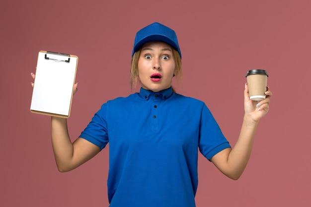 Vista frontale giovane corriere femminile in uniforme blu in posa tenendo la tazza di caffè e blocco note, servizio uniforme consegna donna lavoro lavoratore colore