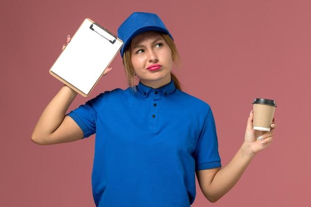 Giovane corriere femminile di vista frontale in uniforme blu che posa tenendo la tazza di caffè e il pensiero del blocco note, lavoro della donna di consegna dell'uniforme di servizio