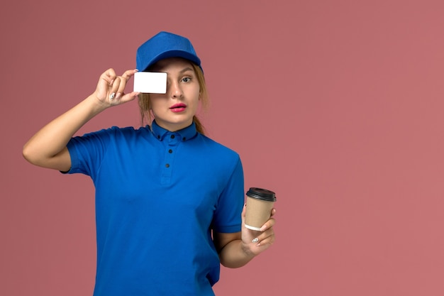 Front view young female courier in blue uniform posing holding cup of coffee and white card, service uniform delivery woman job worker